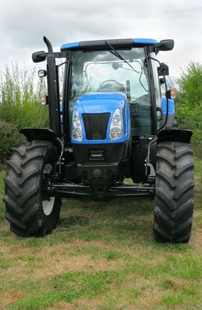 four wheel: New blue and black four wheel drive tractor standing idle in a field. Stock Photo