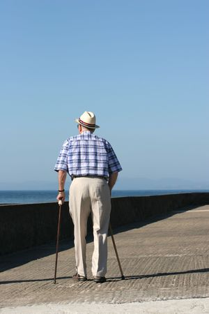 Rear view of an elderly disabled man walking with two walking sticks on a beach promenade.