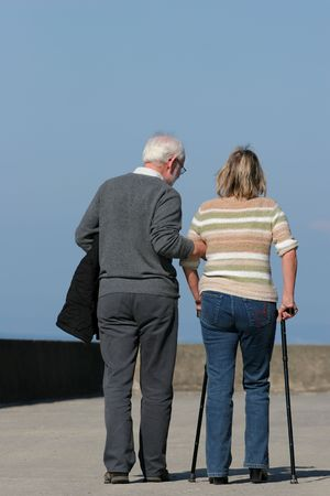 Elderly man helping a middle aged female to walk with walking sticks, with a blue sky to the rear. Stock Photo