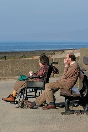 carers: Elderly female in a wheelchair with an elderly man sitting next to her on a promenade bench with his hand to his face. Sea view and coastline, out of focus to the rear, with a blue sky.