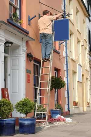 bracket: Middle aged man up a ladder hanging a new blue sign from a cast iron ornate bracket (blank) on the side of a building.