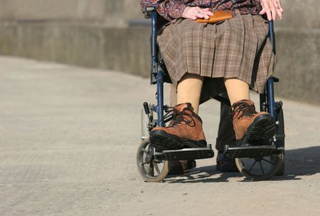 arthritic: Lower body of a an elderly woman sitting in a wheelchair on a pavement, with arthritic hands and wearing large boots.