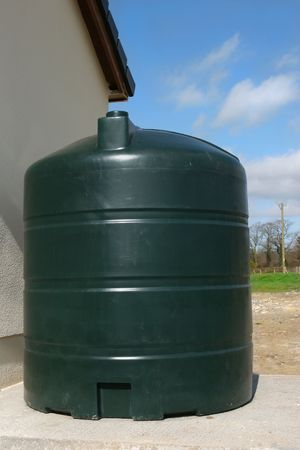 tank: Green plastic diesal tank standing on a bed of concrete at the side of a house. Stock Photo