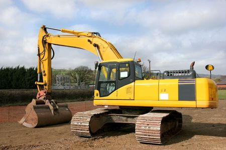 sub station: Yellow digger standing idle on a building construction site with an electricity sub station to the rear. Stock Photo