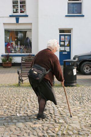 cobble: Anziani di sesso femminile alle prese con un bastone da passeggio a piedi pi� di Cobble pietre in una citt�.