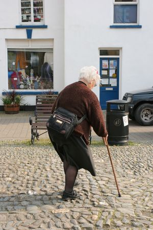 Elderly female struggling with a walking stick walking over cobble stones in a town.