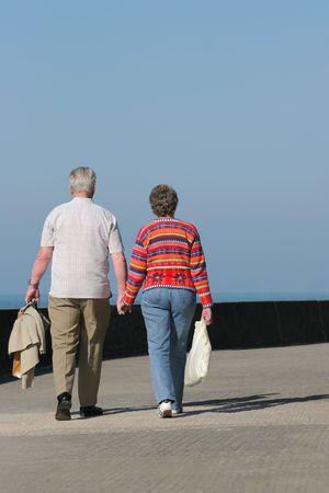 ancianos caminando: Vista trasera de una pareja de edad avanzada y caminar juntos mano a lo largo de un paseo mar�timo. Conjunto contra un cielo azul.