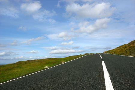 en mont�e: Trempez la route ascendante, la lib�rez outre des voitures, avec des bandes engazonn�es de chaque c�t� avec un ciel bleu et des nuages daltocumulus. Placez dans les balises parc national, Pays de Gales, Royaume-Uni de Brecon.