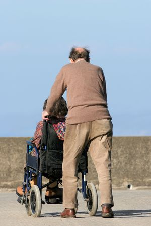 Rear view of an elderly man pushing an elderly female in a wheelchair on a pavement with a blue sky to the rear.