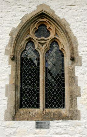 Edad de Piedra: G�tico ventana de vidrio con plomo establecidos dentro de un lavado de cal iglesia de piedra pared.  Foto de archivo