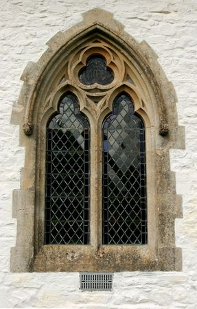 stone arches: Gothic leaded glass window set within a lime washed stone church wall.