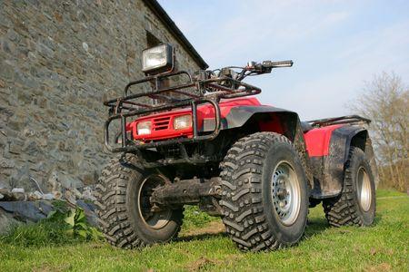 holgaz�n: Cuatro ruedas motrices, rojo y negro quad se cruza de brazos sobre la hierba. Foto de archivo