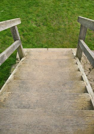 downwards: Old well worn wooden outdoor staircase with the emphasis on going downwards towards grass. Stock Photo