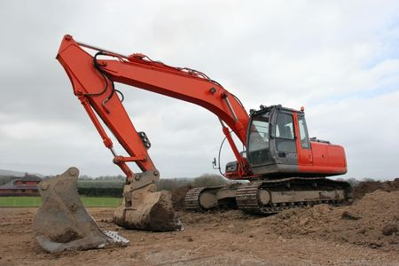 holgaz�n: Gran excavadora naranja se cruza de brazos en tierra fangosa en las zonas rurales con el otro gran campo de repuesto excavadora cubo en primer plano. Frente a un cielo gris nublado.