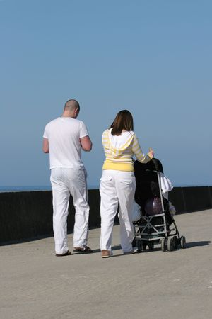 Rear view of a young couple dressed mainly in white, with the female pushing a pram and walking along a beach promenade, blue sky  to the rear. photo