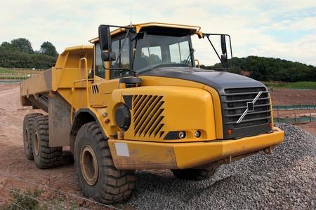 holgaz�n: Dumper de gran cami�n amarillo de inactividad permanente de lodo en una pista en una obra de construcci�n, con un mont�n de grava en la parte delantera.  Foto de archivo