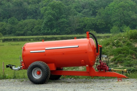 New metal orange muck and slurry tank, used to spray rotted animal excrement onto fields as a fertiliser.