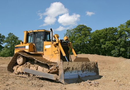 idle: Yellow bulldozer standing idle on rough earth with trees and a blue sky to the rear.