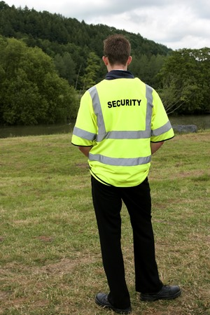 standing alone: Male security guard standing alone in rural countryside. Rear view.