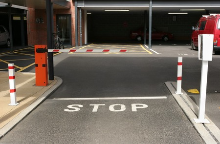 barrier: Entrance to an underground car park with gated barrier and entry machine. Stock Photo