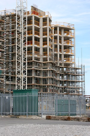 large build: New tall building under construction with scaffolding, against a pale blue sky.