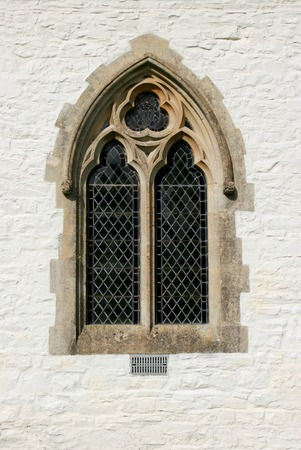 recessed: Gothic leaded glass window on the outside of a church set within a white washed stone wall. Stock Photo
