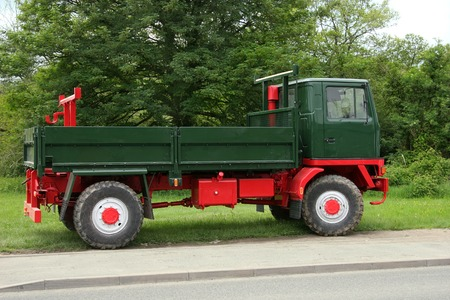 idle: Old classic British green and red truck, standing idle on grass, with trees to the rear.
