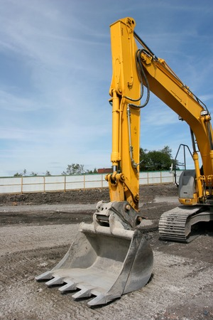idle: Steel excavator bucket on a yellow industrial digger, standing idle on a building site. Stock Photo