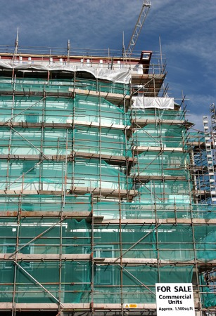 netting: New commercial property under construction with scaffolding and green protective netting covering the facade of the building. Commercial units for sale sign, in view.