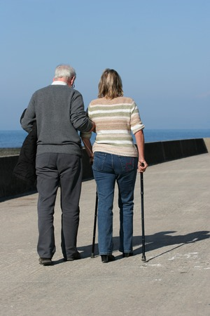 crippled: Elderly man helping a middle aged female to walk with walking sticks, with a blue sky to the rear. Stock Photo