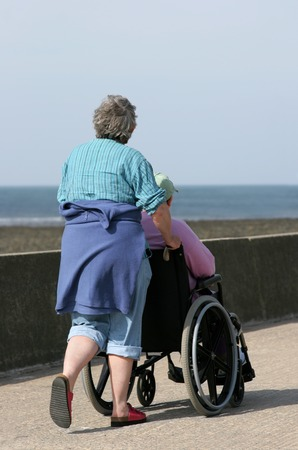 Elderly woman pushing a man in a wheelchair on a seaside promenade. Sea (out of focus) to the rear).