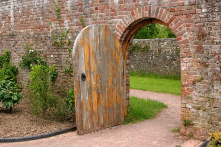 beyond: Old open arched wooden door set into an old red brick wall and leading to a grassed area beyond.