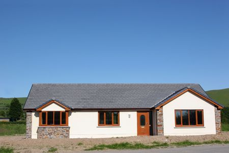 roof framework: New bungalow, rendered and painted cream, with stone facing. Low cost, one level housing, in a rural area against a blue sky.