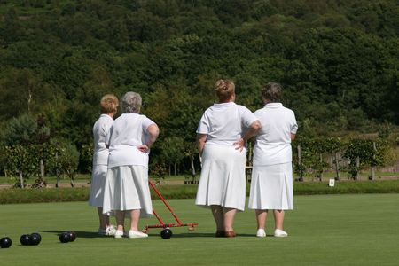 gatherer: Four elderly females (rear view) dressed  in white lawn bowling outfits and standing on a bowling green. One of the ladies is holding a red metal ball gatherer. Trees and shrubs to the rear.