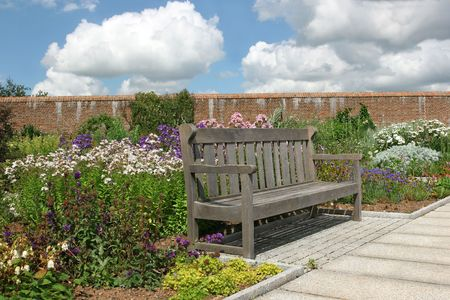 Old oak wooden bench within a red brick walled garden in summer full of flowers and shrubs. Blue sky and cumulus clouds to the rear. photo