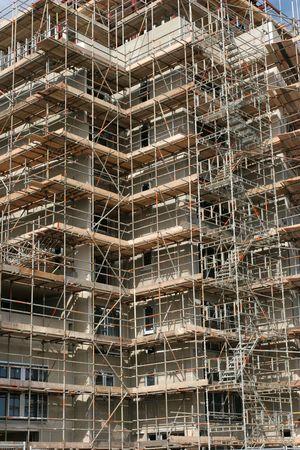 cement pole: Complex scaffolding on a new skyscraper under building construction.