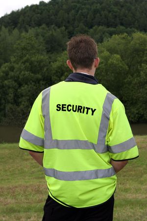 standing alone: Male security guard wearing standing alone in rural countryside. Rear view. Stock Photo