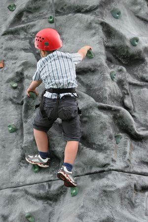 Young boy climbing on a rock training face, wearing a safety harness and red helmet. photo