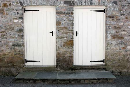 ferreteria: Dos viejos de color blanco con puertas de madera negro y ironmongery pasos establecidos en un antiguo muro de piedra.