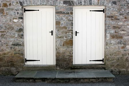 Two white old wooden doors with black ironmongery and steps set into an old stone wall. Stock Photo