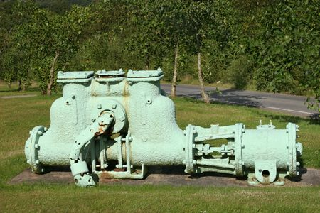 Permanent: Oude metalen gietijzer waterpomp pastel permanent groen geschilderd bevestigd op beton, met bomen en struiken naar achteren.