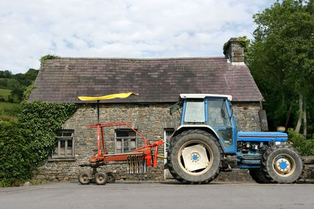 spreads: Blue tractor with a red swather (picks up, aerates, and spreads out cut hay). To the rear is a derelict small stone barn Stock Photo