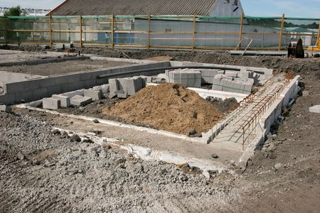 Concrete foundations for a new building on a construction site with sand pile, reinforcing mesh and concrete blocks.