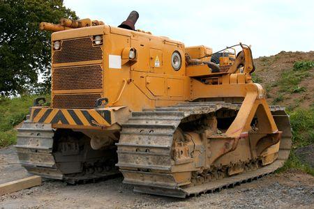 holgaz�n: Las grandes bulldozer amarillo permanente de inactividad en la tierra �spera.  Foto de archivo
