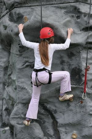 succeeding: Young girl climbing upwards on a rock training face wearing a safety harness and red hard hat. Stock Photo