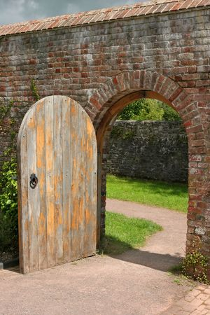 Old open arched wooden door set into an old red brick wall and leading to a grassed area beyond.