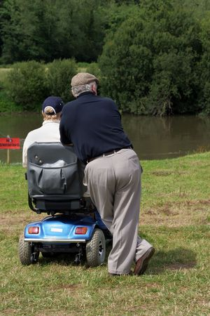 Two elderly men, one sitting on an electric  mobility scooter and one standing with both looking at a river bank in rural countryside. Rear view. Stock Photo