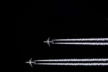 Two jet aircraft flying in a horizontal and parallel formation with smoke trails, set against a black sky background. Stock Photo