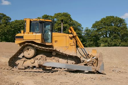 Yellow bulldozer (side view) standing idle on rough earth with trees and a blue sky to the rear. photo