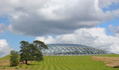 sustainable tourism: Futuristic eco dome made of glass panels set into a grass hillside. Location, National Botanical Gardens of Wales, United Kingdom.